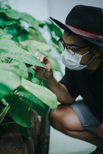 Young man wearing mask touching plant