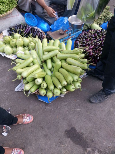 Low section of people buying vegetables at market