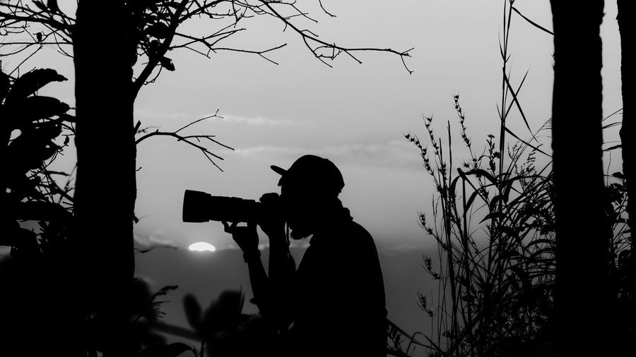 Silhouette man photographing against sky