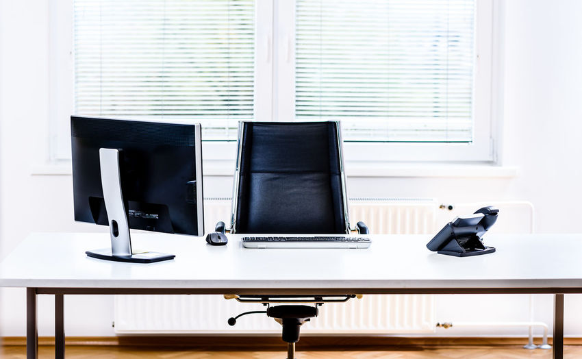 Computer and landline phone on desk in office