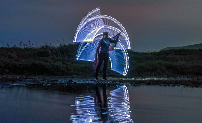 Woman standing by lighting paintings reflecting on lake