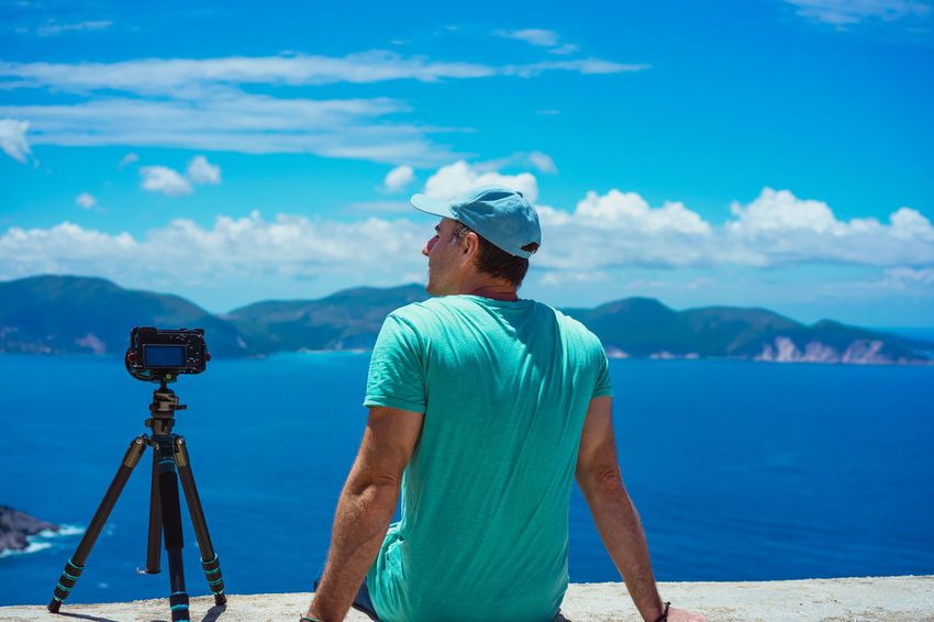Summer holiday visiting Greece. Male photographer enjoying to capture time lapse cloudscape, coastline and sea with digital camera on tripod. Europe travel Capture The Moment Coastline Landscape Beauty In Nature Camera - Photographic Equipment Cloud - Sky Day Enyoing The Moment Leisure Activity Lifestyles Mature Men Men Mountain Nature One Person Outdoors Photography Themes Real People Rear View Scenics - Nature Sea Sky Standing Stillness In Time Viewpoint Water