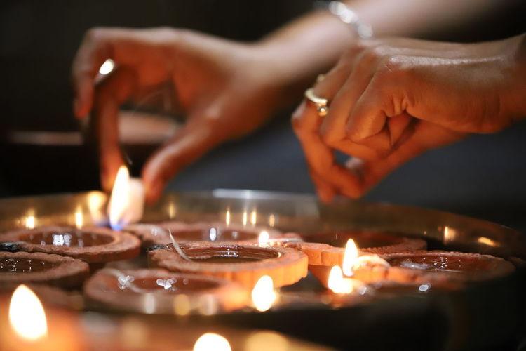 Close-Up Of Woman Hand With Illuminated Diyas