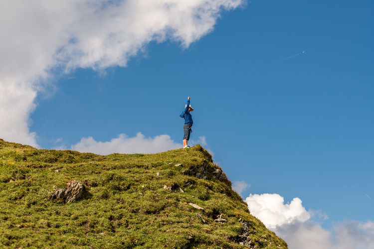 Low Angle View Of Boy Standing At The Edge Of Mountain Against Sky
