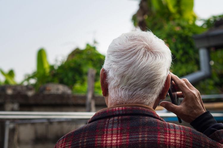Back view of elderly man using smartphone in his garden.