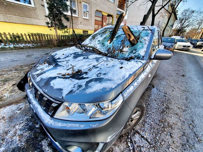Abandoned car in city during winter