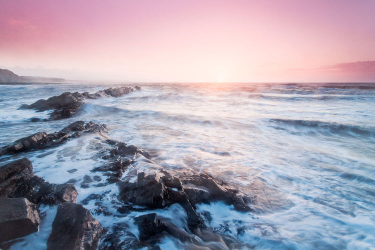 Scenic view of sea waves splashing on rocks during sunset