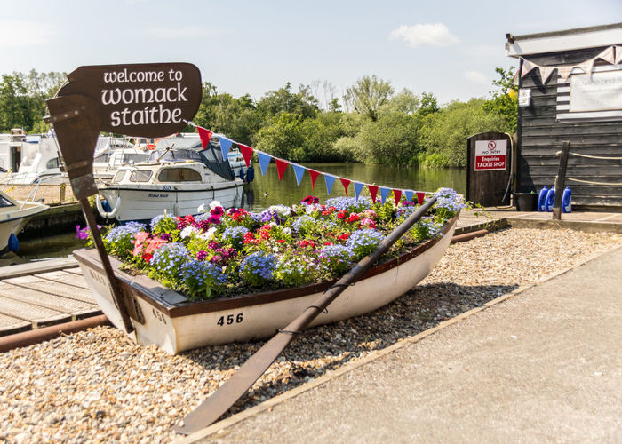 Womack Staithe Boat Bunting Cloud - Sky Communication Day Flags Flower Display Flowering Plant Flowers Information Land Vehicle Mode Of Transportation Motor Vehicle Nature No People Outdoors Plant Road Sign Sky Text Transportation Tree Western Script