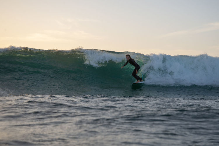 Sport Adventure Aquatic Sport Water Motion Sea Leisure Activity One Person Surfing Extreme Sports Skill  Wave Sky Balance Waterfront Challenge Real People Lifestyles Men Power In Nature Outdoors