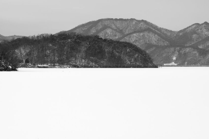 black and white image of snow-covered lake, Uiamho Lake in Chuncheon, Gangwondo, South Korea Black & White ChunCheon Cold Lake Cold Weather Gongjicheon Snow Land Uiamho Lake Winter Winter Landscape Beauty In Nature Black And White Blackandwhite Bw Clear Sky Cold Cold Temperature Copy Space Day Landscape Mountain Mountain Range Nature No People Outdoors Scenics Sky Snow Snow-covered Snow-covered Lake Snowing Tranquil Scene Tranquility Travel Destinations Tree Winter Winter Lake Winter Land Winter Time