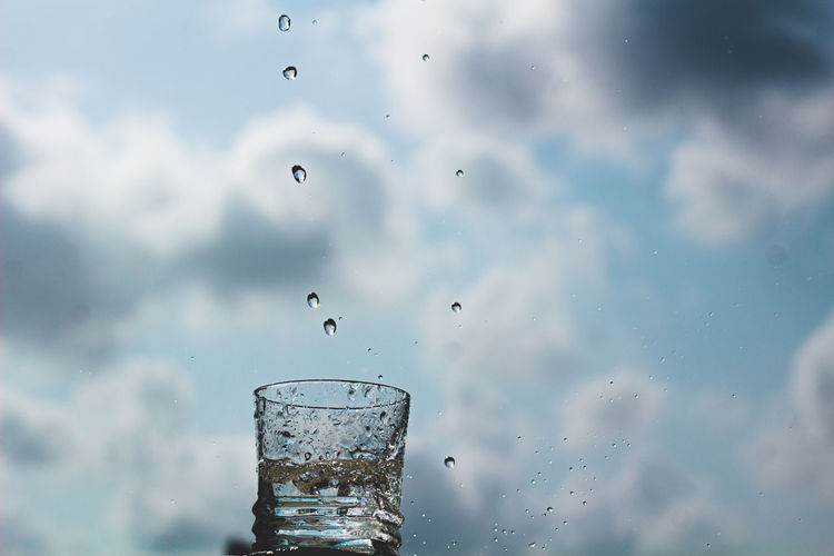 Close-up of water drops on glass against sky