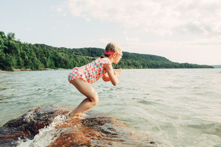 Side view of girl jumping in river