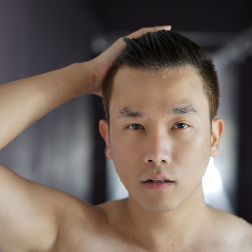 Close-up portrait of shirtless man with wet hair