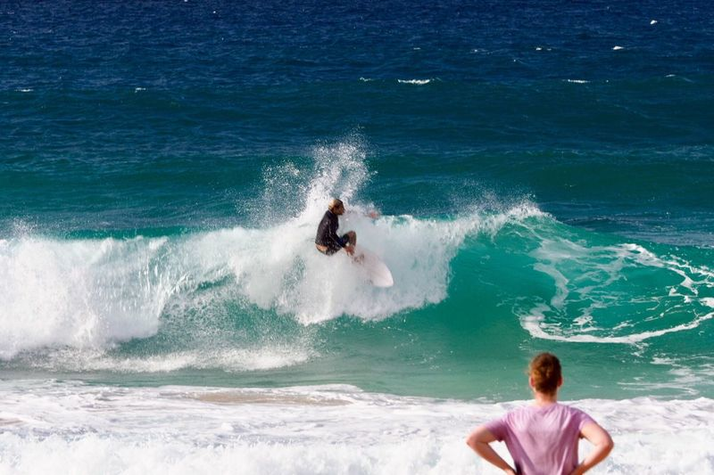 Man looking at surfer surfing in sea