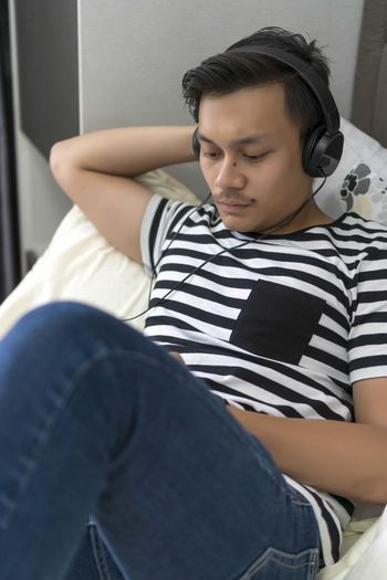 Young Malay guy looking at the phone relaxing at the bed Casual Clothing One Person Striped Real People Sitting Lifestyles Leisure Activity Indoors  Headphones Young Adult Three Quarter Length Young Men Front View Relaxation Music Technology Listening Men Jeans Contemplation