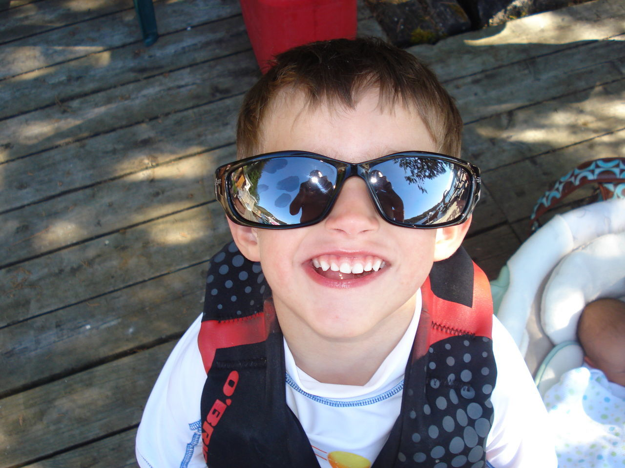 High Angle Portrait Of Smiling Boy Wearing Sunglasses While Sitting On Wood