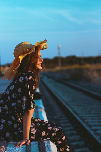 Side view of smiling young woman wearing hat sitting on railroad station platform against sky during sunset