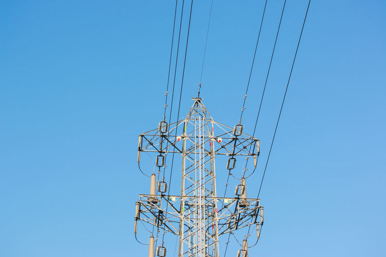 Mast electrical power line against blue sky. Background Blue Cable Danger Electric Electrical Electricity  Energy Engineering Environment Generation Generator High Industrial Industry Internet Landscape LINE Mast Metal Network Outdoor Phone Power Signal Silhouette Sky Spread Steel Structure Sun Technology Tower Transmission Voltage Watt Wireless Copy Space Power Line  Electrical Equipment Electricity Pylon Day Sunlight Connection