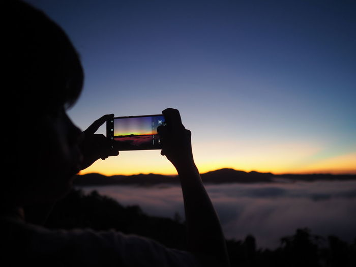 Portrait of man using mobile phone against sky during sunset