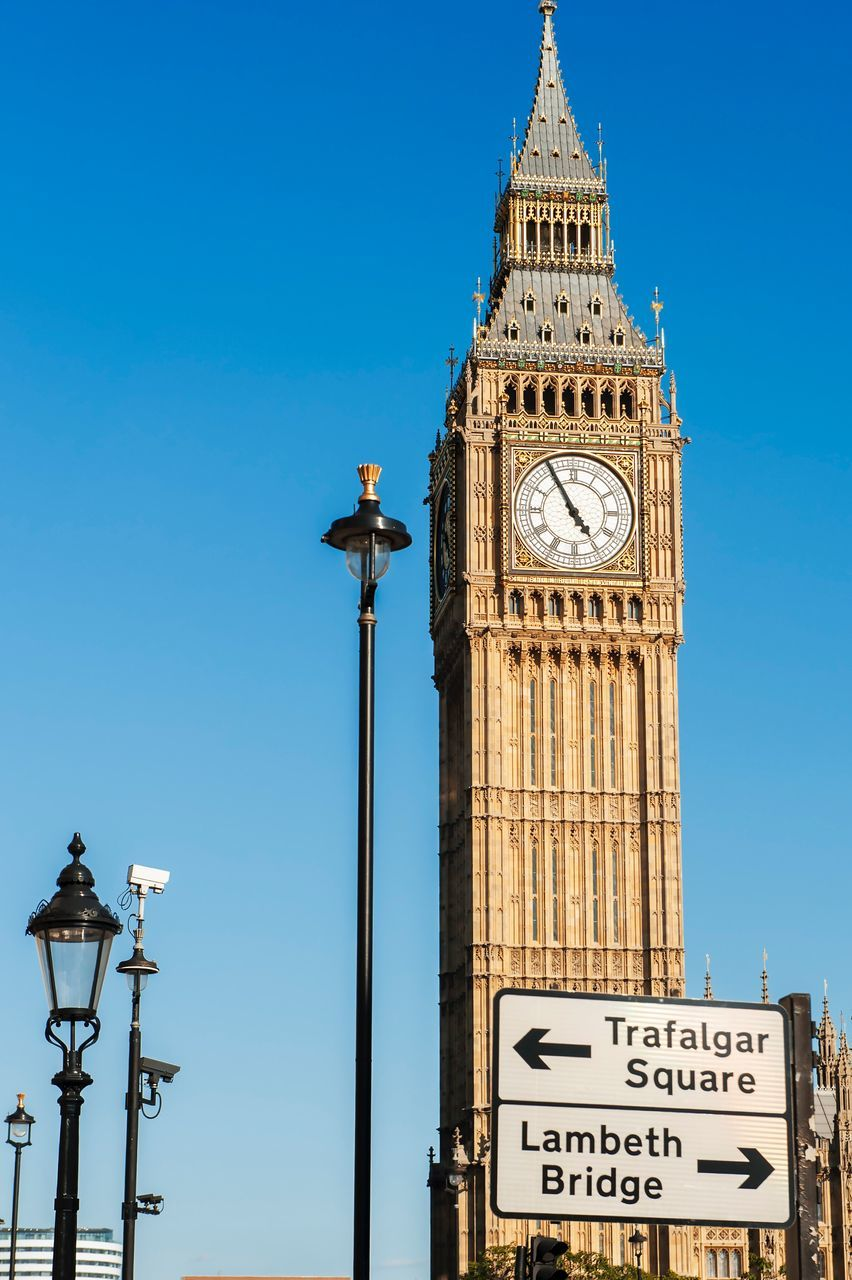 text, low angle view, tower, blue, day, communication, travel destinations, clear sky, clock tower, outdoors, architecture, built structure, no people, building exterior, sky, road sign, clock