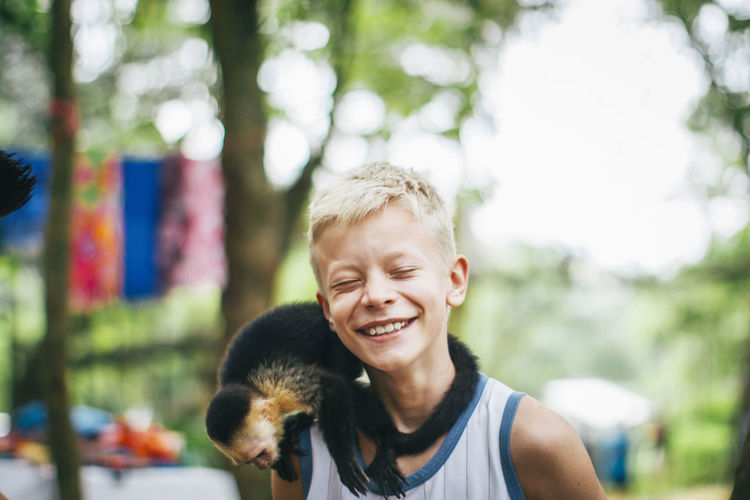 Close-Up Of Cheerful Boy With Capuchin Monkey On Shoulder
