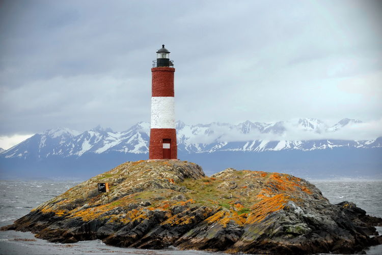 Lighthouse by sea and mountains against sky