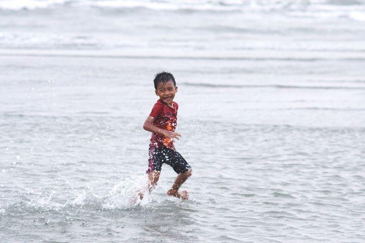 Cheerful Boy Running At Sea