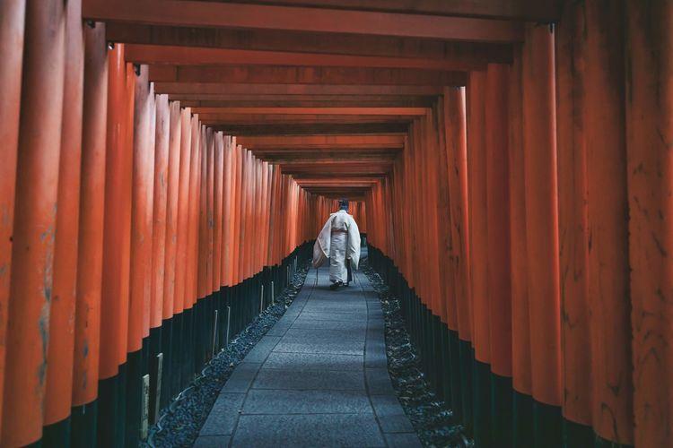 Rear view of man walking in corridor of building