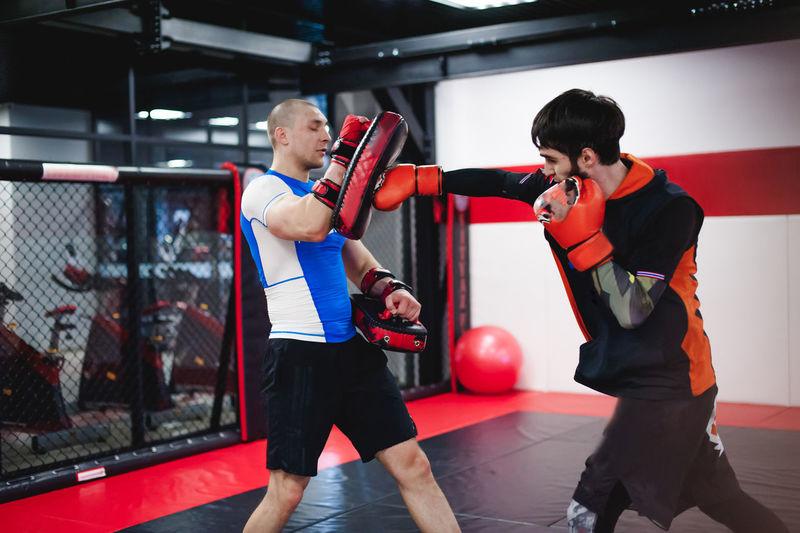 Men practicing in boxing ring