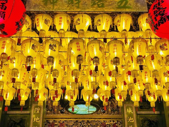Illuminated lanterns hanging in temple at night