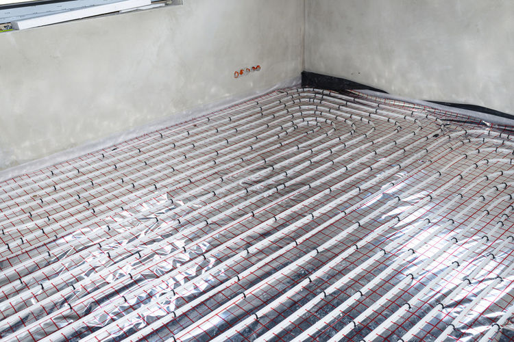 White pipes of underfloor heating systems, distributed in an individual family house on foil.