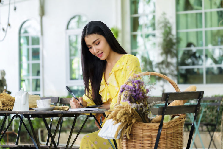 Beautiful woman sits writing on note book in garden