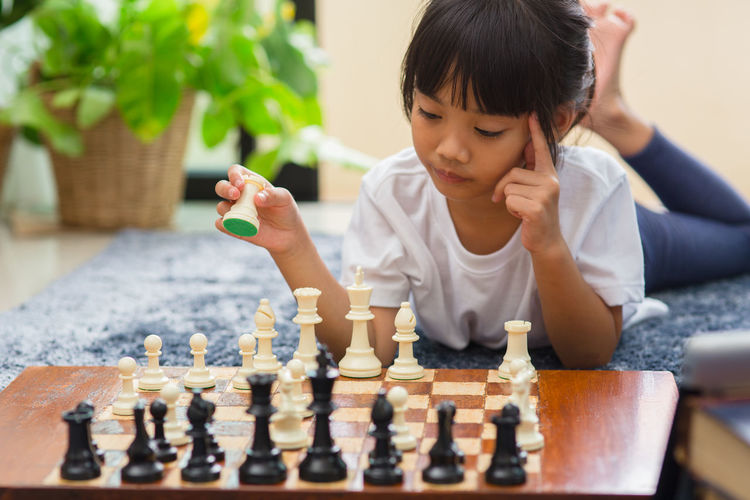 Full length of boy playing on chess board