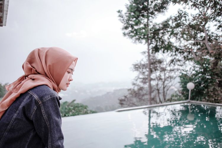 Side view of woman wearing hijab looking at infinity pool