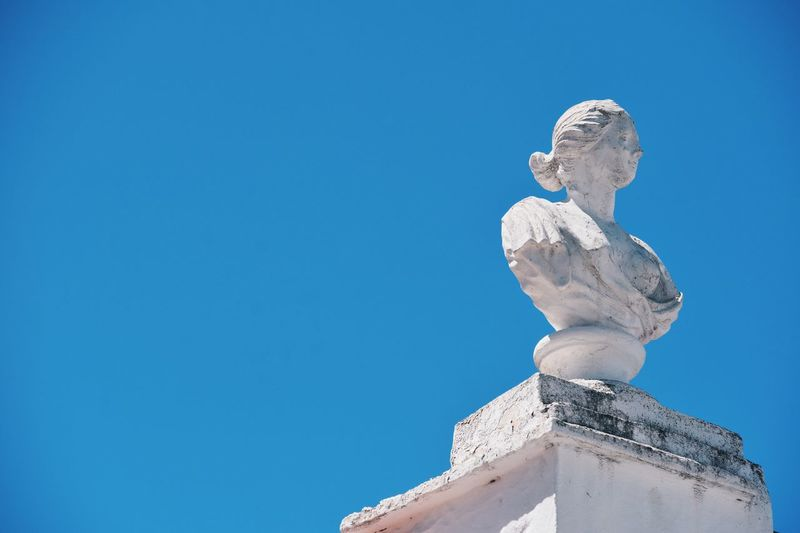 Low angle view of statue on column against clear sky