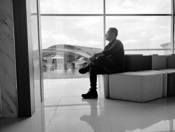 Reflection of man sitting on glass window at airport
