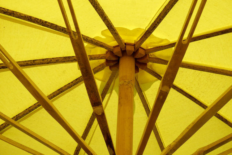Low angle view of yellow parasol against sky