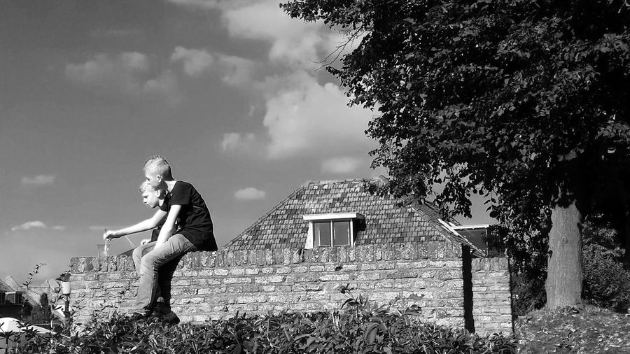Black & White Brick Wall Friends Sitting Outside Sitting On Top Of The World Summertime Architecture Black And White Brothers Building Exterior Built Structure Day Full Length Looking Down From Above Nature One Woman Only Outdoors People Real People Sky Talking Tree Two Boys Young Adult