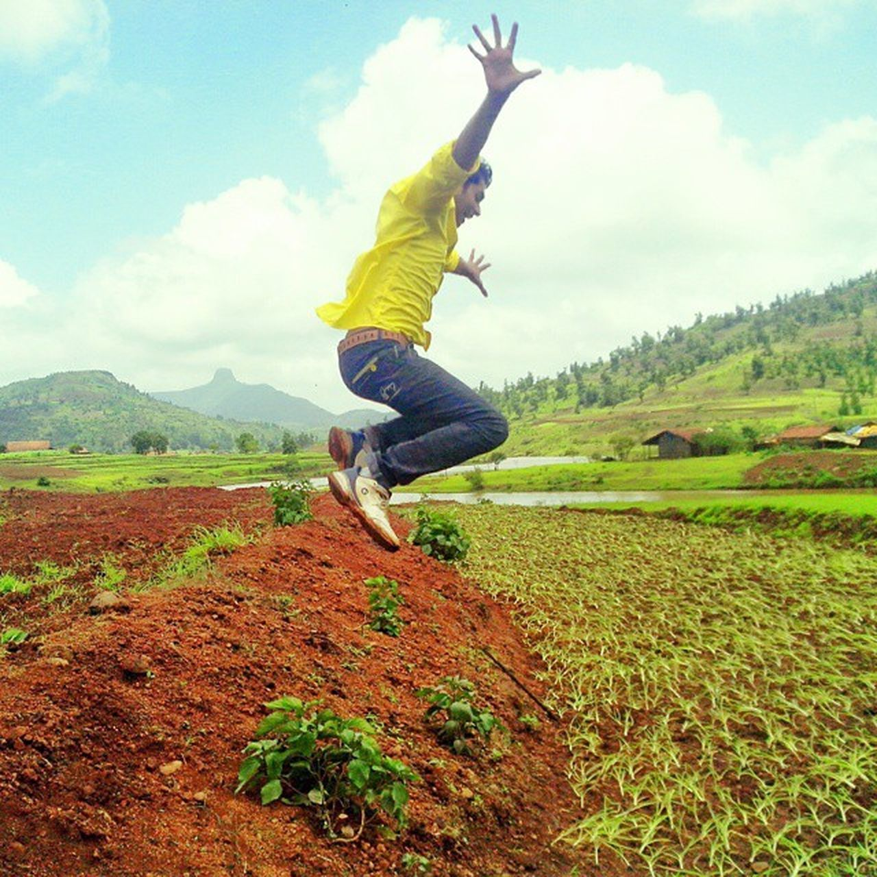 sky, full length, mid-air, field, cloud - sky, motion, casual clothing, one person, day, fun, jumping, outdoors, landscape, nature, grass, tree, beauty in nature, energetic, young adult, adult, people