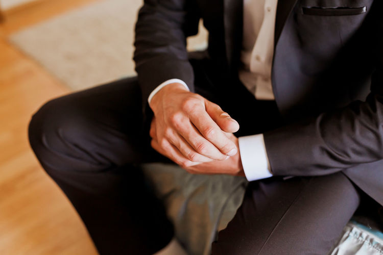 Midsection of businessman getting dressed
