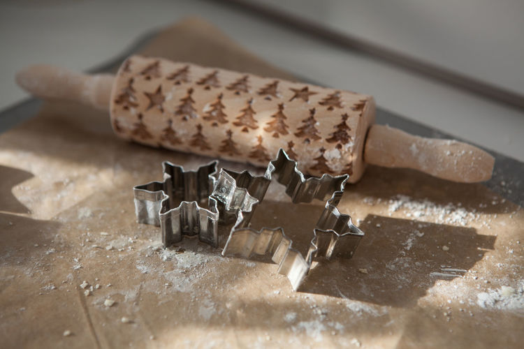 High angle view of rolling pin and cookie cutters on cutting board