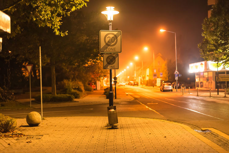 Speed limit sign on gas light in city at night