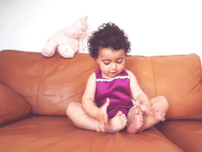 Full Length Of Cute Baby Girl Playing On Sofa At Home