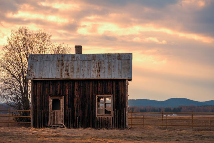 Abandoned barn on field against sky during sunset