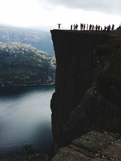 People on cliff at sea against sky