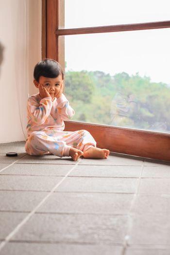 Full length of girl sitting on floor at home