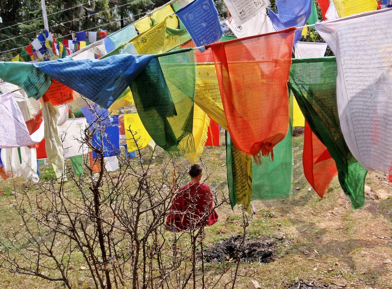 Rear View Of Monk Walking Below Religious Prayer Flags
