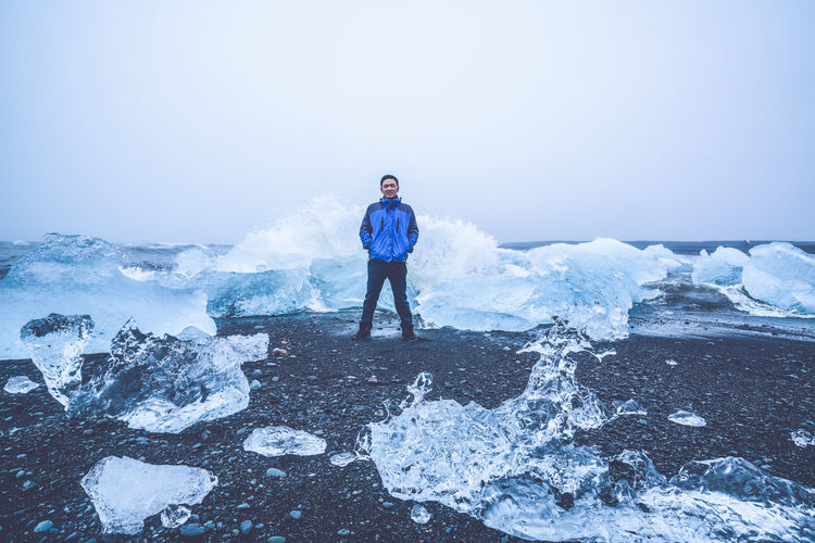Portrait of man standing by ice formations at beach