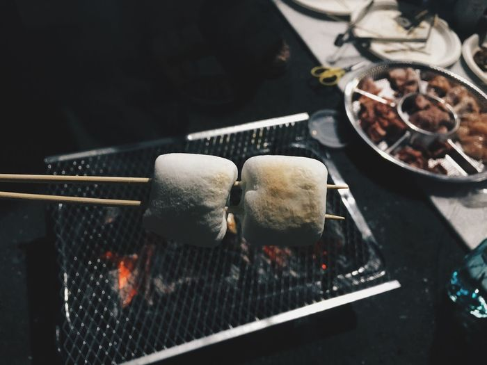 High Angle View Of Marshmallows Being Cooked On Barbecue Grill At Market Stall