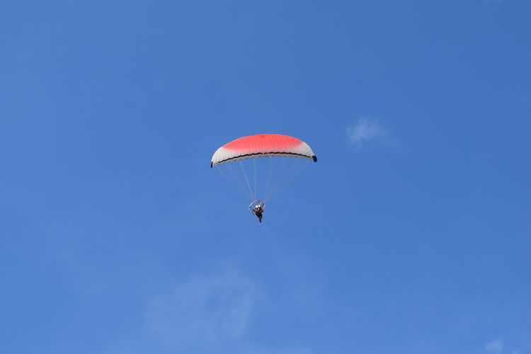 Low angle view of person parachuting against blue sky